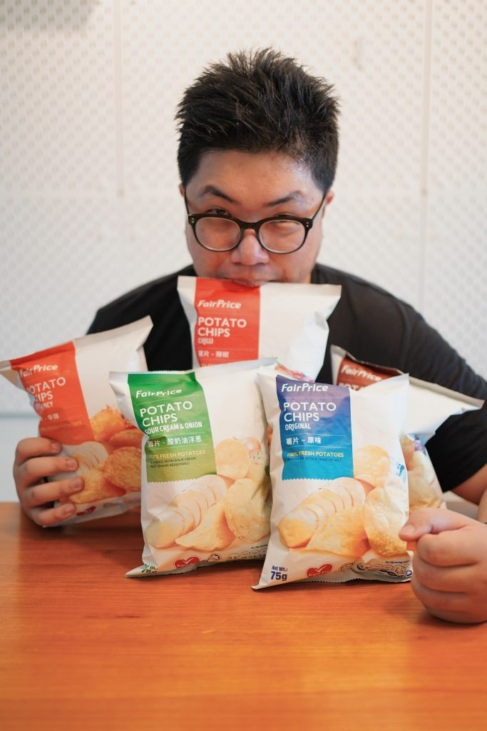 Posing with packs of potato chips from NTUC